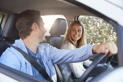 Young couple going on holiday in a car smiling to each other Royalty Free Stock Images