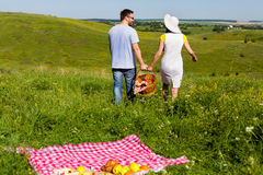 Young couple going home arter picnic. Back view of young couple going home arter picnic, they left fruits and blanket on the grass Royalty Free Stock Photos