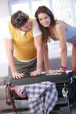 Young couple going to summer vacation packing bag Stock Photos