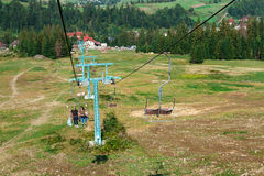 Young couple going up on ski lift, Carpathian mountains background. Young beautiful couple going down on ski lift, Carpathian mountains background. Copy space Stock Photography