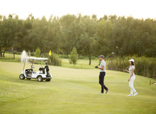 Young couple by golf cart Royalty Free Stock Image