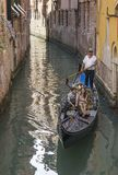 Young couple on a gondola, Venice, Italy. Europe, in a narrow canal royalty free stock photo