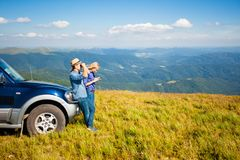 The tourists are navigating. The young couple got lost in the mountains and tries to find out their location by using phone and binoculars Royalty Free Stock Photos