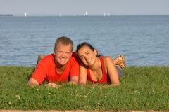 Young couple on the grass on the beach in summertime stock photo