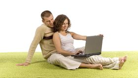 Young couple on green carpet with laptop Stock Photos
