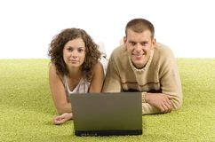 Young couple on green carpet with laptop Royalty Free Stock Photos
