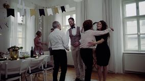Young couple greeting parents or grandparents on a indoor birthday party. stock video