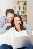Young couple grinning at content on the laptop Royalty Free Stock Photos