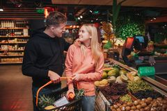 Young couple in grocery store. Cheerful man and woman look at each other and smile. He hold grocery basket in hands. stock photography