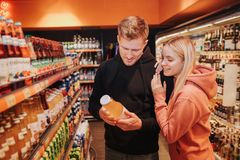 Young couple in grocery store. They look together at juice bottle in hands of man. Young woman lean to guy`s shoulder. Young couple in grocery store. They look stock images