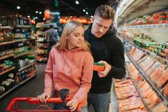 Young couple in grocery store. Man hold caviar in hands and look down. Woman stand besides and hold trolley. Choosing royalty free stock photography