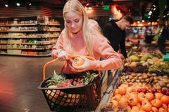 Young couple in grocery store. Nice woman put persimmon into grocery basket and look down. Guy stand behind. He pick up royalty free stock images