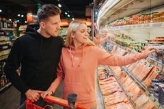 Young couple in grocery store. They pick sea food together. Young woman point on mussels jar and smile. Man stand royalty free stock photography