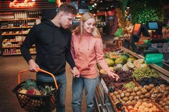 Young couple in grocery store. They pick up fruit together. Exotical and different kind of berries on shelfs. stock images