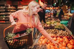 Young couple in grocery store. She reach to persimmon with hand and smile. Model hold basket. Guy stand behind and has stock image