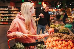 Young couple in grocery store. Woman hold pomegranat in hand and look at guy. He has grapes in hands. Smiling to each stock photography