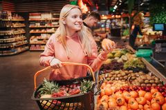 Young couple in grocery store. Woman stand in front and hold basket with orange persimmon. Cheerful positive model. Guy royalty free stock image
