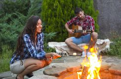 Young couple with guitar near fire outdoors Stock Images