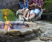 Young couple with guitar near fire outdoors Royalty Free Stock Photography