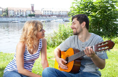 Young couple with guitar outside Royalty Free Stock Photos