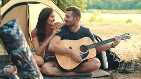 Young couple with guitar in tent stock footage