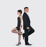 Young couple with guns. Man and women with a guns isolated on a grey background, scene from sinema, back to back royalty free stock photos