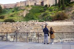 Young couple: a guy and a girl with a backpack visiting the Roman theater of Malaga. Ruin. stock images