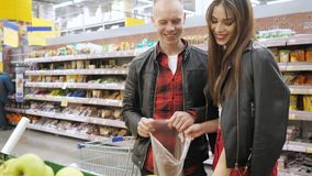 Young couple buys pears in a supermarket, girl puts pears in plastic bag. stock video