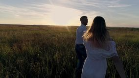 Young couple guy and girl running across the field towards the sunset stock footage