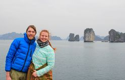 Young couple guy and girl in sportswear hugging and laughing happily against the background of the cliffs of Ha Long Bay during th stock image