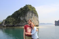Young couple guy and girl in sportswear hugging and laughing happily against the background of the cliffs of Ha Long Bay during th royalty free stock images