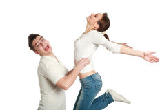 Young couple, guy with jumping up girl, studio, isolated Royalty Free Stock Photography
