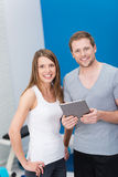 Young couple at the gym monitoring their exercise royalty free stock photo