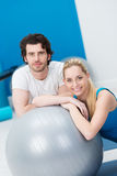 Young couple in a gym with a Pilates ball Royalty Free Stock Image