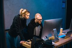 young couple of hackers looking at computer stock image