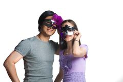 Young couple with half masks Royalty Free Stock Image