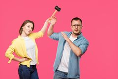 young couple with hammer looking at camera isolated