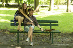 A young couple hand-feed a squirrel on a Park bench. Happy. Royalty Free Stock Images