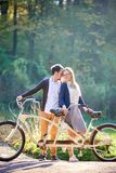 Young couple, handsome man and attractive woman on tandem bike in sunny summer park or forest. stock photos