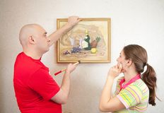 Young couple hanging art picture on wall at Royalty Free Stock Photo