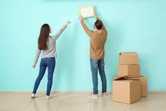 Young couple hanging picture on wall in their new house royalty free stock photography