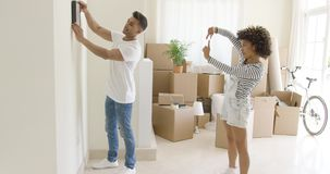 Young couple hanging pictures in their new home stock video
