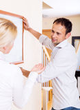 Young couple hangs a picture Royalty Free Stock Photos