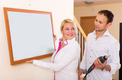 Young couple hangs a picture Royalty Free Stock Image
