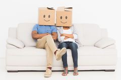 Young couple with happy smiley boxes over faces Stock Photos