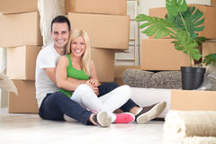 Young couple happy for their new home. Hugging with boxes in background Royalty Free Stock Images