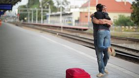 Young couple happy to meet again in the train station, girl runs to meet her boyfriend and throws a suitcase stock video