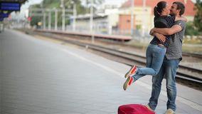 Young couple happy to meet again in the train station, girl runs to meet her boyfriend and throws a suitcase, twist on. Hands, happy meeting stock footage