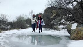 Young couple has fun in park and rides on frozen puddle covered with melted water. Slow motion. Young couple has fun in park and rides on frozen puddle covered stock video footage