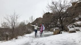 Young couple has fun in park and rides on frozen puddle covered with melted water. Water splashes fly apart and youth laughs cheer stock video